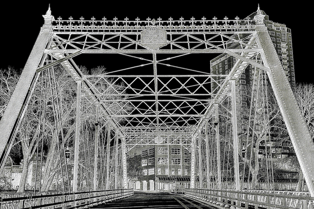 The Merriam Street Bridge is a truss bridge that spans the east channel of the Mississippi River between Nicollet Island and the east bank of the river in Minneapolis, Minnesota. The bridge was originally built in 1887 by King Iron Bridge Company as one of the four spans of the Broadway Avenue Bridge. When the Broadway Avenue Bridge was reconstructed in 1987, one span was preserved and moved to Nicollet Island. The truss span is actually decorative; the bridge is supported by a beam from underneath.<br /> <br /> The original Broadway Avenue Bridge was one of the fanciest bridges on the Mississippi River. It featured finials on each top corner and a band of scrolls, crosses, and lines between them. The horizontal struts and guard railings used X-shapes as a pattern. Each end of the bridge has a hexagonal cast iron plate embossed with the date and the designer of the bridge. The bridge now serves as a connector between parkland on Nicollet Island and the Saint Anthony Main development on the east bank, allowing good opportunities for visitors to stroll across the river.