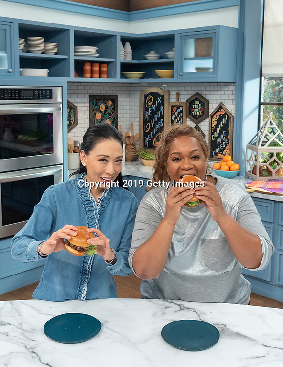 Chefs Sunny Anderson and Judy Joo are photographed with Judy's Krazy Korean Burger on the set of Food Network's The Kitchen in Montclair, New Jersey on February 13th, 2019. (Photo by Kris Connor/Getty Images for OK! Magazine) Sunny Anderson, Judy Joo, tv set, food network, burger, african american, asian, female chef, female, burger, bun, food photography, food porn, television, Food television, portrait, environmental portrait, magazine, posing, vertical