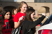 Iraan High School cheerleader Lexie Coe writes words of support for the football team before their travels to Arlington for the state championship game in Iraan, Texas on December 14, 2016. (Cooper Neill for The New York Times)