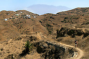 One hiker walks in the ancient path used by sheperds in the direction of Faja da Agua village. On the background massive Fogo island is omnipresent with its 2829 metres vulcano.