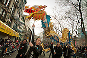 A gold and turquoise dragon snakes down the parade route.