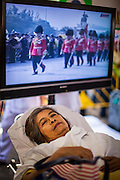 """05 DECEMBER 2012 - BANGKOK, THAILAND: A woman who passed out in the heat rests in the Red Cross tent while the """"Trooping of the Colors"""" is broadcast on a TV behind her on the Royal Plaza Wednesday. They were waiting to see Bhumibol Adulyadej, the King of Thailand, before his public audience at the Mukkhadej balcony of the Ananta Samakhom Throne Hall. December 5 is a national holiday. It's also celebrated as Father's Day. Celebrations are being held across the country to mark the birthday of Bhumibol Adulyadej, the King of Thailand.    PHOTO BY JACK KURTZ"""