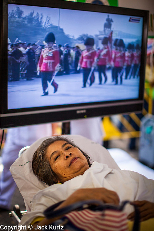 "05 DECEMBER 2012 - BANGKOK, THAILAND: A woman who passed out in the heat rests in the Red Cross tent while the ""Trooping of the Colors"" is broadcast on a TV behind her on the Royal Plaza Wednesday. They were waiting to see Bhumibol Adulyadej, the King of Thailand, before his public audience at the Mukkhadej balcony of the Ananta Samakhom Throne Hall. December 5 is a national holiday. It's also celebrated as Father's Day. Celebrations are being held across the country to mark the birthday of Bhumibol Adulyadej, the King of Thailand.    PHOTO BY JACK KURTZ"