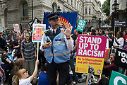 Police Liaison Officer informs people sitting down outside Downing Street that they can stay for five more minutes at Peoples Assembly National Demonstration Against Theresa May and Austerity - Not One Day More - Tories Out, on Saturday July 1st in London, United Kingdom. Tens of thousands of people gathered to protest in a march through the capital protesting against the Conservative Party cuts. Following the recent General Election where the Labour Party gained seats, while the Conservative Party lost their majority, the mood in the country has been one where an anti-austerity movement is growing as people become tired with Tory rule.