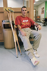 Man sitting in waiting room of fracture clinic in hospital with leg in plaster,