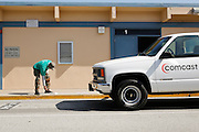 """A Comcast employee paints """"Stay Back"""" in the parking lot's drop off zone with a stencil during Comcast Cares Day at Curtner Elementary School in Milpitas, California, on April 27, 2013. (Stan Olszewski/SOSKIphoto)"""