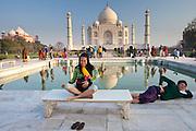 Tourists sit on Diana bench at The Taj Mahal mausoleum southern view with reflecting pool, Uttar Pradesh, India
