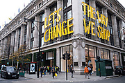 Letschange the way we shop sign outside Selfridges as the national lockdown ends and the new three tier system of local coronavirus restrictions begins, shoppers head out to Oxford Street to catch up on shopping as non-essential shops are allowed to reopen on 2nd December 2020 in London, United Kingdom. Many shoppers wear face masks outside on the street as a precaution as there are so many people around.