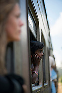 On the train to Ella, Sri Lanka, a young Sri Lankan girl looks out the window. In the foreground a European woman also looks out a window. (April 9, 2017)