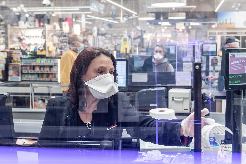 L'Intermarché de La Loupe, le 18 mars 2020<br /> Une caissière travaille derrière une vitre en plexiglass afin de se protéger et protéger les clients qui passent à sa caisse.