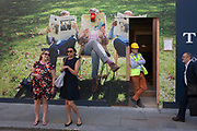 Two laughing women wait to cross Jermyn Street, in front of a construction hoarding for fashion brand Charles Tyrwhitt, on 6th July 2016, in London, United Kingdom. As a workman leans against the wooden structure and another man walks towards the women, the ladies themselves share a moment of mirth beneath the scene of men reading the corporate newspapers.