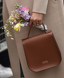 Meghan Markle holds her bag and some flowers during a walkabout in Belfast after a visit to the Crown Bar in the city centre.