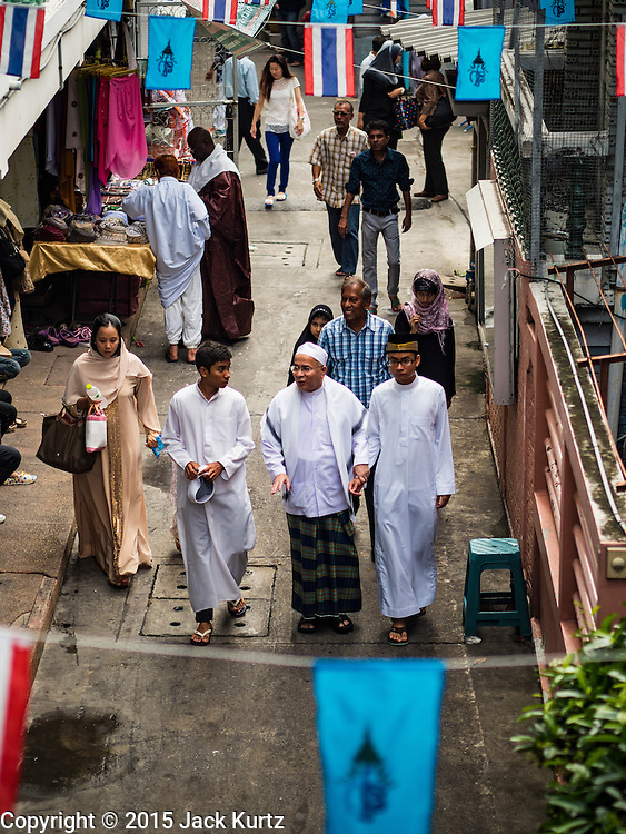 24 SEPTEMBER 2015 - BANGKOK, THAILAND:  People walk into Haroon Mosque before the celebration of Eid al-Adha at Haroon Mosque in Bangkok. Eid al-Adha is also called the Feast of Sacrifice, the Greater Eid or Baqar-Eid. It is the second of two religious holidays celebrated by Muslims worldwide each year. It honors the willingness of Abraham to sacrifice his son, as an act of submission to God's command. Goats, sheep and cows are sacrificed in a ritualistic manner after services in the mosque. The meat from the sacrificed animal is supposed to be divided into three parts. The family retains one third of the share; another third is given to relatives, friends and neighbors; and the remaining third is given to the poor and needy.    PHOTO BY JACK KURTZ
