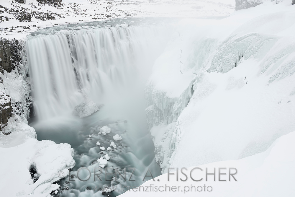 The waterfall Dettifoss in a long time exposure on a white and cloudy afternoon in wintertime, Iceland