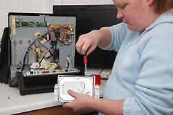 Woman with a mild learning disability working as a trainee computer technician, shown here changing hard drive, helped into employment by the Ready 4 Work team, Nottinghamshire County Council