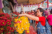 """09 FEBRUARY 2013 - BANGKOK, THAILAND: A woman prays in Wat Mangkon Kamalawat, the largest Chinese temple in Chinatown in Bangkok. Bangkok has a large Chinese emigrant population, most of whom settled in Thailand in the 18th and 19th centuries. Chinese, or Lunar, New Year is celebrated with fireworks and parades in Chinese communities throughout Thailand. The coming year will be the """"Year of the Snake"""" in the Chinese zodiac.    PHOTO BY JACK KURTZ"""
