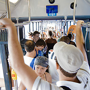 People standing in a crowded bus after the beach.