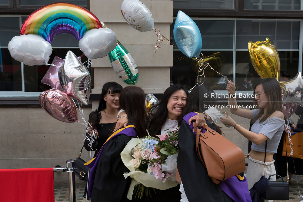 Friends and family of Hillary Chung,, a 21 year-old Law graduate from Hong Kong, celebrate her graduation with a 2:1 degree outside the London School of Economics (LSE) after her graduation ceremony, on 22nd July 2019, in London, England.