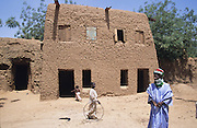 Traditional Husa village house..The implementation of Islamic Sharia Law across the twelve northern states of Nigeria, centres upon Kano, the largest Muslim Husa city, under the feudal, political and economic rule of the Emir of Kano. Islamic Sharia Law is enforced by official state apparatus including military and police, Islamic schools and education, plus various volunteer Militia groups supported financially and politically by the Emir and other business and political bodies. Fanatical Islamic Sharia religious traditions  are enforced by the Hispah Sharia police. Deliquancy is controlled by the Vigilantes volunteer Militia. Activities such as Animist Pagan Voodoo ceremonies, playing music, drinking and gambling, normally outlawed under Sharia law exist as many parts of the rural and urban areas are controlled by local Mafia, ghetto gangs and rural hunters. The fight for control is never ending between the Emir, government forces, the Mafia and independent militias and gangs. This is fueled by rising petrol costs, and that 70% of the population live below the poverty line. Kano, Kano State, Northern Nigeria, Africa