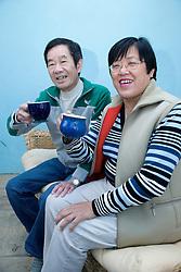 Older couple sitting on the sofa drinking tea,