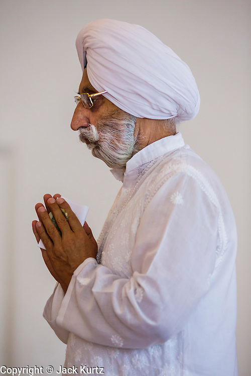 12 AUGUST 2012 - PHOENIX, AZ: A member of the Phoenix Sikh community prays as he enters the Gurdwara during Sunday services at the Guru Nank Dwara Ashram Sikh temple in central Phoenix. Guru Nank Dwara Ashram is the oldest of three Sikh temples in the Phoenix area. There are about 1,500 Sikh families in the area. Memorials have been held throughout the week to honor the Sikhs killed in the mass shooting in Wisconsin last week. Sunday's service included several mentions of the massacre and was attended by a number of people active in the Phoenix interfaith community.   PHOTO BY JACK KURTZ