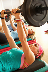 Woman Lifting Barbell at Fitness Class