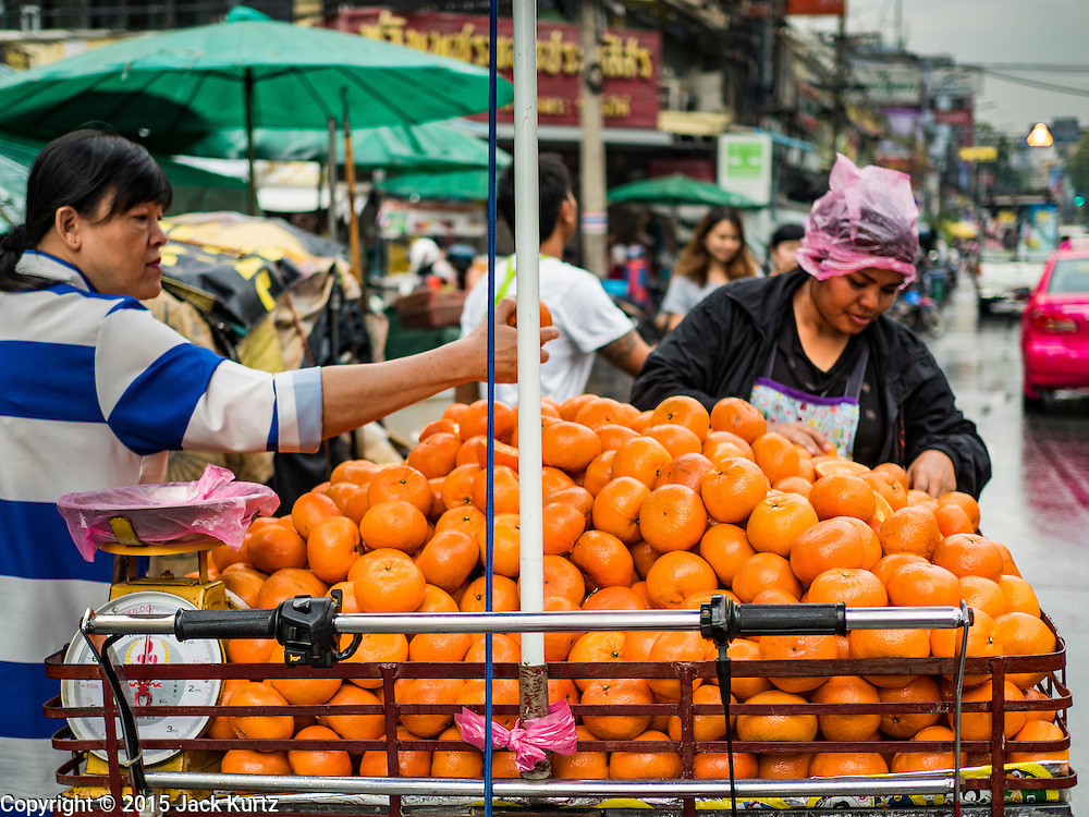 23 DECEMBER 2015 - BANGKOK, THAILAND: A vendor sells oranges in the street market in Banglamphu. Banglamphu Market (also spelled Bang Lamphu) is close to Bangkok's backpacker haunts of Khao San Road. The market is a popular place for knock off designer clothes and street food. The market is an informal collection of street stalls and sidewalk vendors. Bangkok city officials have plans to evict the vendors, close the market and gentrify the neighborhood. This would follow closing similar markets on Maharat Road and Saphan Lek.       PHOTO BY JACK KURTZ