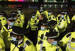 © Licensed to London News Pictures. 15/03/2021. London, UK. A large group of police officers detain a protester outside Scotland Yard as anger continues over the policing of Saturday's Sarah Everard vigil at Clapham Common in south London. Photo credit: Peter Macdiarmid/LNP