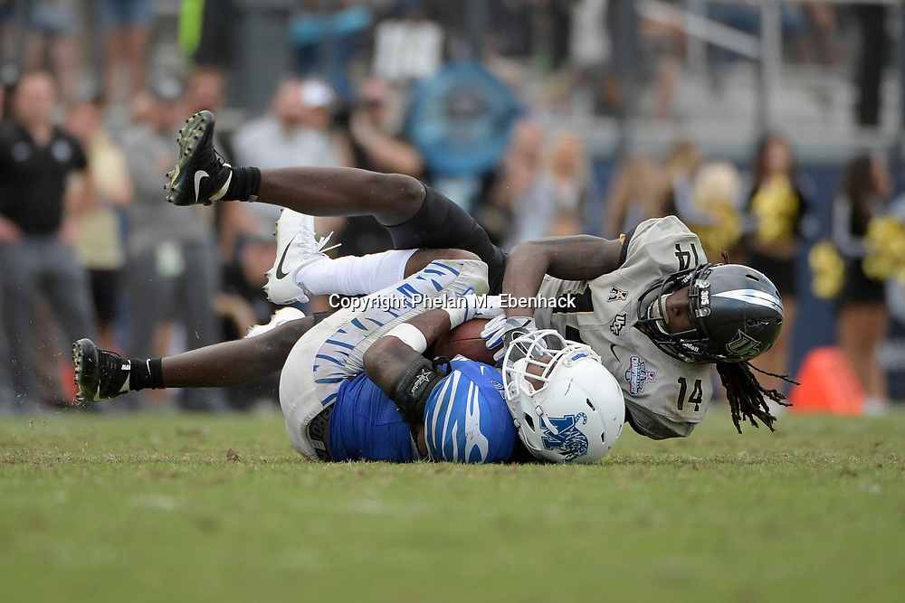 Memphis wide receiver Anthony Miller (3) is tackled by Central Florida defensive back Nevelle Clarke (14) after catching a pass during the second half of the American Athletic Conference championship NCAA college football game Saturday, Dec. 2, 2017, in Orlando, Fla. Central Florida won 62-55. (Photo by Phelan M. Ebenhack)