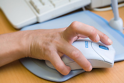 Woman with disability at work using a computer mouse; Nottinghamshire Coalition for Disabled People (NCDP)