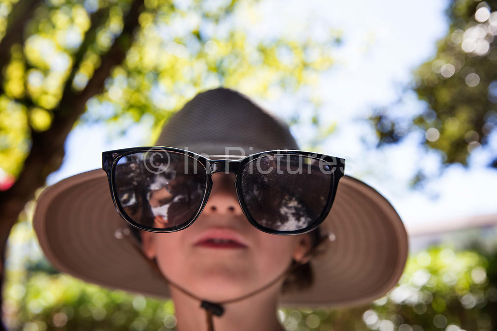 Young boy wearing large adult sunglasses and a wide brimmed hat as protection from the sun on 23rd August 2018 in Lagrasse, France. Sunglasses are more than just fashion accessories. They play an important role in protecting our eyes from damaging UV radiation. UK and Europe the standards on sunglasses are very strict and insist that they block 99-100% of UV radiation.