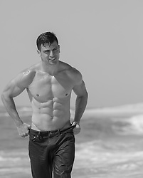 hot muscular man by the ocean in jeans