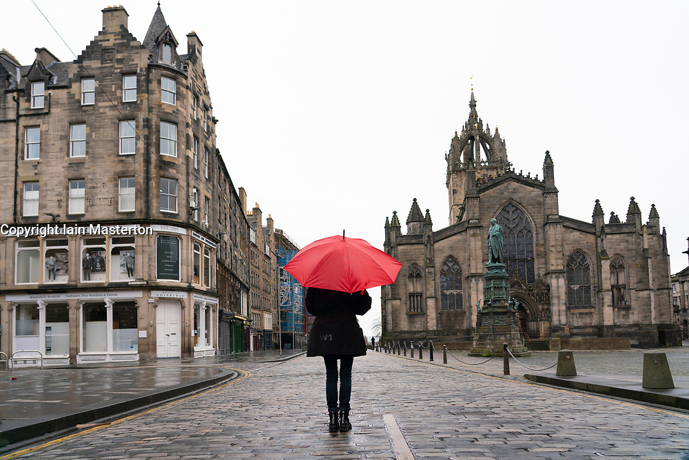 Woman holding red umbrella in rain on the Royal Mile in Old Town of Edinburgh, Scotland, UK