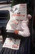 While still a Portuguese colony, a 1990s Macau gentleman reads his newspapers from under the pages of newsprint, on 10th August 1994, in Macau, China.