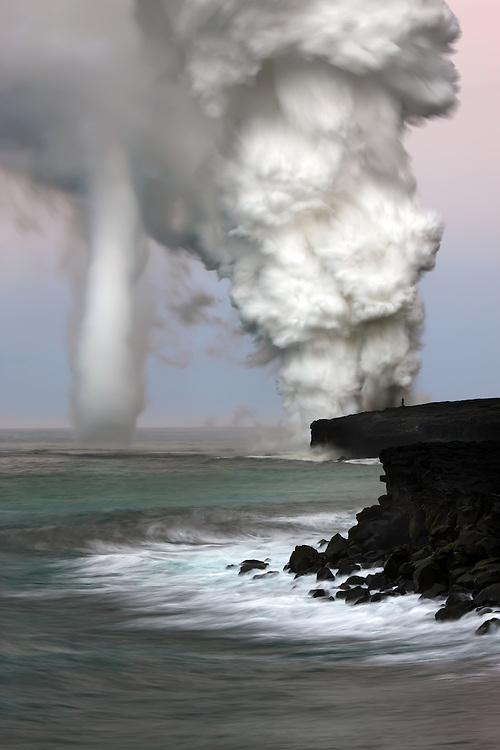 A rapidly rising updraft created by the billowing plume, spins into an impressive vortex.  A videographer standing near the ocean entry gives one a feel of relative scale.