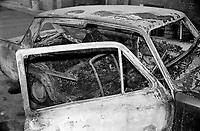 Burnt-out shell of a car in which two bodies were found at Downing Street, off Shankill Road, Belfast, N Ireland on 23rd January 1977. The victims, stabbed & shot, were Thomas John Boston, Crumlin, Co Antrim and John Joseph Lowther, a native of Co Mayo, Rep of Ireland, but who had been living in Bolton, Lancashire, UK, for 20 years. Boston, a Protestant and an Orangeman, and Lowther, a Roman Catholic, worked for the same building company, had been out drinking together and ended up in a loyalist club on the Shankill Road. The loyalist gang which picked them up included senior UDA members, Jim Craig and Arthur Bettice, who were later shot by their own organisation. 197701230025.<br /> <br /> Copyright Image from Victor Patterson,<br /> 54 Dorchester Park, <br /> Belfast, UK, BT9 6RJ<br /> <br /> t1: +44 28 9066 1296 (from Rep of Ireland 048 9066 1296)<br /> t2: +44 28 9002 2446 (from Rep of Ireland 048 9002 2446)<br /> <br /> m: +44 7802 353836<br /> <br /> e: victorpatterson@me.com<br /> www.victorpatterson.com<br /> <br /> Please see my Terms and Conditions of Use at www.victorpatterson.com. It is IMPORTANT that you familiarise yourself with them.<br /> <br /> Images used on the Internet must be visibly watermarked i.e. © Victor Patterson<br /> within the body of the image and copyright metadata must not be deleted. Images <br /> used on the Internet have a size restriction of 4kbs and will be chargeable at current<br />  NUJ rates unless agreed otherwise.<br /> <br /> This image is only available for the use of the download recipient i.e. television station, newspaper, magazine, book publisher, etc, and must not be passed on to any third <br /> party. It is also downloaded on condition that each and every usage is notified within 7 days to victorpatterson@me.com<br /> <br /> The right of Victor Patterson to be identified as the author is asserted in accordance with The Copyright Designs And Patents Act (1988). All moral rights are asserted.