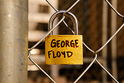 """02 APRIL 2021 - MINNEAPOLIS, MINNESOTA: A lock with George Floyd's name on it locked to the perimeter fence around the Henneping County Courthouse. The lock is one of hundreds of locks bearing the names of people of color killed by police on the fence. The installation is called """"Locks 4 Stolen Lives"""". Protesters are keeping a 24 hour presence in front of the Hennepin County Courthouse in Minneapolis during the murder trial of former Minneapolis Police Officer Derek Chauvin. Chauvin is on trial for murdering George Floyd in 2020. Floyd's death, while restrained and in police custody, set off a summer of racial justice protests across the United States.       PHOTO BY JACK KURTZ"""