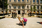 10 JULY 2020 - DES MOINES, IOWA: Polk County deputies watch a Black Lives Matter supporter chalk a sidewalk in front of the county's historic courthouse. About 75 people, members and supporters of Black Lives Matter gathered at the Polk County Courthouse to protest law enforcement harassment of Black Lives Matter. They also showed support for several members of BLM who made their first appearance in court following their arrest at a BLM protest last week. BLM has become very active in Des Moines in the wake of the police killing of George Floyd in Minneapolis in May.      PHOTO BY JACK KURTZ