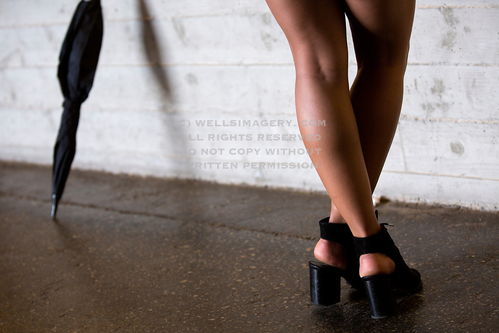 Image of a woman's legs and an umbrella on a rainy day in San Pedro, California, America west coast by Randy Wells