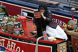 © Licensed to London News Pictures. 06/05/2013, London, UK. A boater works on her canal boat during the Canalway Cavalcade waterway festival at Little Venice in London, Monday, May 6, 2013. Photo credit : Sang Tan/LNP