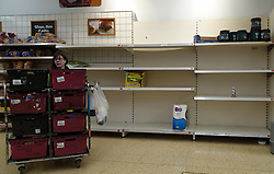 © Licensed to London News Pictures. 23/07/2021. London, UK. A Sainsbury's staff member walks past empty shelves in a Sainsbury's store in London. The government has announced that daily contact testing will be rolled out to workplaces in the food sector, so staff who have been pinged by the COVID-19 app can keep working if they test negative rather than isolating. This is because a number of supermarkets are reporting empty shelves as they, wholesalers and hauliers are struggling to ensure enough food and fuel supplies, after the COVID-19 NHS app alerted workers to isolate after being in contact with someone with COVID-19. Photo credit: Dinendra Haria/LNP