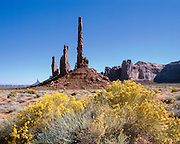 The Totem Pole rock spire surrounded by rabbit bush in Monument Valley on the Navajo Indian Reservation in northern Arizona and southern Utah