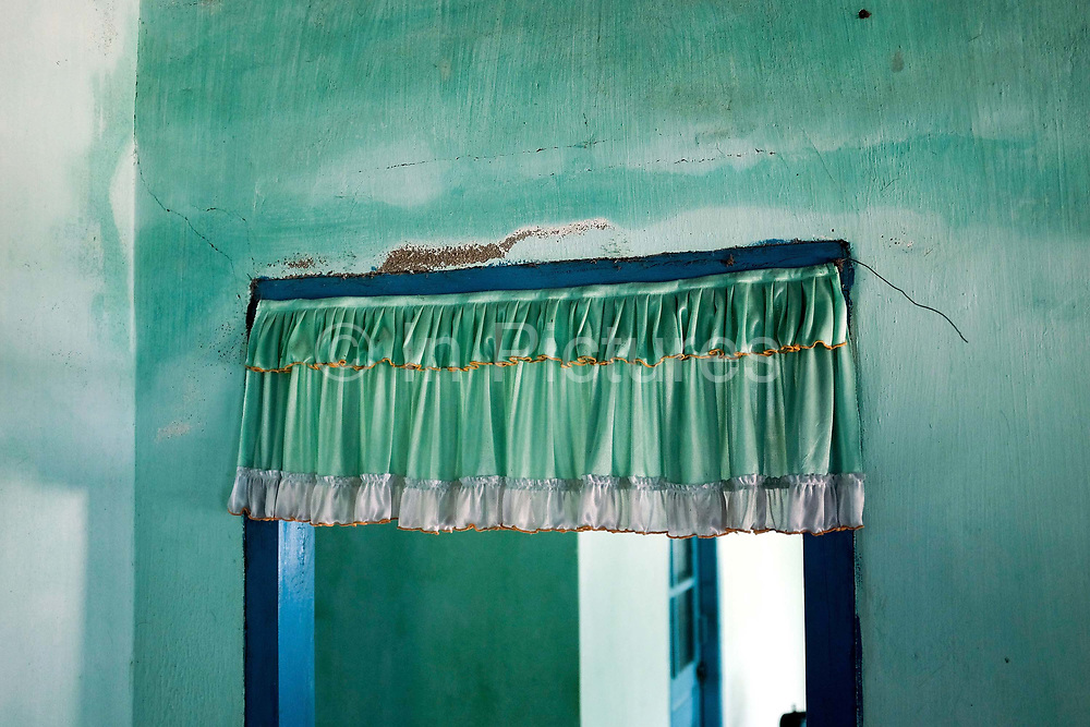 A green shiny curtain hanging over a doorway in a home in the Vietnamese Hindu Cham weaving village of My Nghiep village, Ninh Thuan province, Central Vietnam.