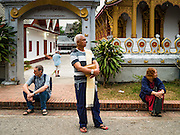 "11 MARCH 2016 - LUANG PRABANG, LAOS:  A Lao man flanked by tourists waits for Buddhist monks to pass him during the morning tak bat in Luang Prabang. Luang Prabang was named a UNESCO World Heritage Site in 1995. The move saved the city's colonial architecture but the explosion of mass tourism has taken a toll on the city's soul. According to one recent study, a small plot of land that sold for $8,000 three years ago now goes for $120,000. Many longtime residents are selling their homes and moving to small developments around the city. The old homes are then converted to guesthouses, restaurants and spas. The city is famous for the morning ""tak bat,"" or monks' morning alms rounds. Every morning hundreds of Buddhist monks come out before dawn and walk in a silent procession through the city accepting alms from residents. Now, most of the people presenting alms to the monks are tourists, since so many Lao people have moved outside of the city center. About 50,000 people are thought to live in the Luang Prabang area, the city received more than 530,000 tourists in 2014.      PHOTO BY JACK KURTZ"