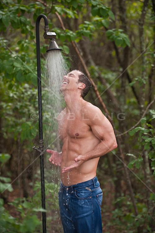 man enjoying an outdoor shower in the woods
