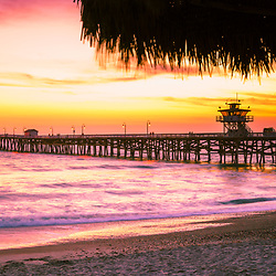 San Clemente CA pier panorama sunset photo. Inlcudes a straw tiki umbrella and beautiful purple and orange colors along the Southern California coast and Pcific Oceaan. San Clemente is a popular coastal city in Orange County in the United States of America. Copyright ⓒ 2017 Paul Velgos with all rights reserved.