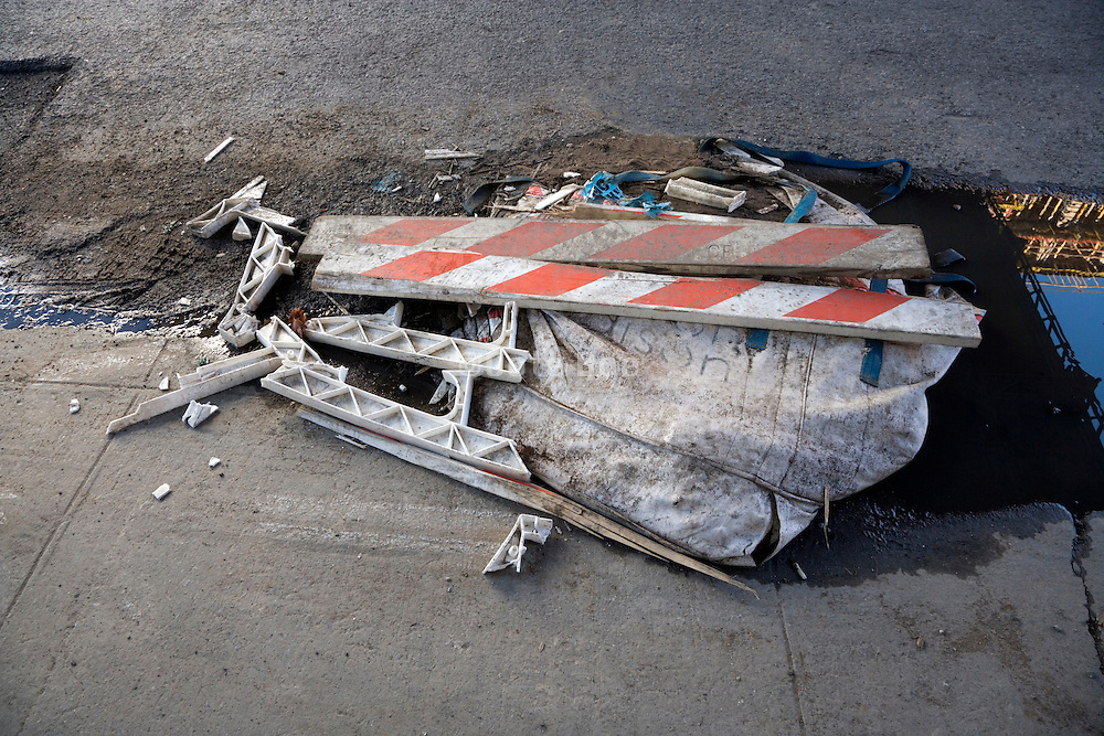 a destroyed traffic sawhorse on the side of the road
