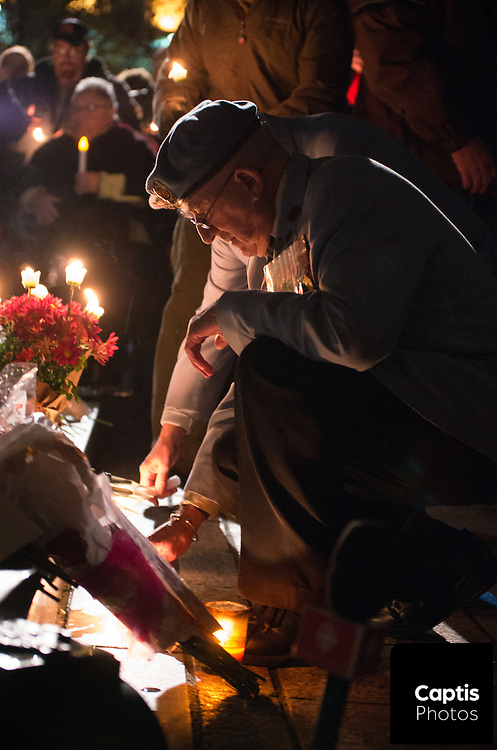 A veteran places a candle next to the cenotaph at the National War Memorial. October 25, 2014.