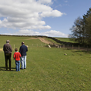 Three generations of men, grandad, dad, young son, stopping for a minute in the peaceful environment, looking at the future, thinking of the past.<br />