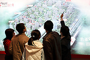 An agent shows potential buyers the layout of a new residential development at a real estate fair in Shanghai, China on 15 March, 2009. For the past decade, Shanghai has underwent the largest reconstruction in recorded history, over 20 million square meters of land, approximately a third of Manhattan, were developed between year 200 and 2005 alone. Despite that however, housing prices have seen a rapid increase, putting the prospect of owning a decent sized home out of the reach of ordinary Chinese citizens, especially middle to low income families.